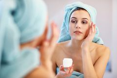 Young woman standing in bathroom and applying face cream in the morning. Picture showing young woman in the bathroom stock photos