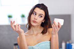 Young woman standing in bathroom and applying face cream in the morning. Picture showing young woman in the bathroom royalty free stock photography