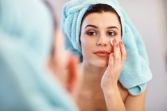 Young woman standing in bathroom and applying face cream in the morning. Picture showing young woman in the bathroom stock photo