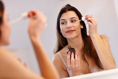 Young woman standing in bathroom and applying face serum in the morning. Picture showing young woman in the bathroom stock photo