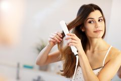 Young woman standing in bathroom in the morning. Picture showing young woman looking in bathroom mirror stock images