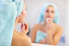 Young woman standing in bathroom in the morning. Picture showing young woman looking in bathroom mirror royalty free stock images