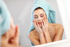 Young woman standing in bathroom in the morning. Picture showing young woman looking in bathroom mirror royalty free stock photo