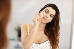 Young woman standing in bathroom in the morning. Picture showing young woman looking in bathroom mirror stock image