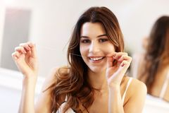 Young woman using dental floss in bathroom. Picture showing young woman looking in bathroom mirror stock images