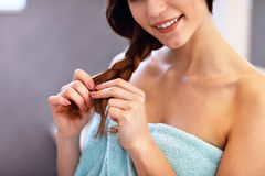 Young woman standing in bathroom and brushing hair. Picture showing young woman taking care of hair in bathroom royalty free stock photos
