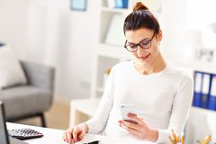 Woman working in her home office. Picture showing young woman working in her home office Stock Photos
