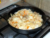 Cabbage stewed with meat in a frying pan on a gas stove royalty free stock image
