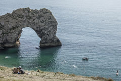 Durdle Door - the arch, blue waters and people kissing. The picture shows Durdle Door - the limestone arch some people on the beach and on the meadows above the Royalty Free Stock Images