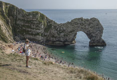 Durdle Door - the arch, blue waters and people. The picture shows Durdle Door - the limestone arch some people on the beach and on the meadows above the beach Royalty Free Stock Photos