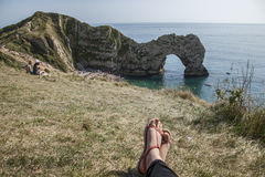 Durdle Door - the arch, blue waters and feet in sandals. The picture shows Durdle Door - the limestone arch and two feet of a person sitting on a meadow at the Stock Image