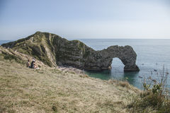 Durdle Door limestone arch, England - blue waters and meadows. The picture shows Durdle Door - the natural limestone arch in Dorset, England. There`s the edge Royalty Free Stock Photography