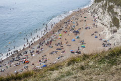 Durdle Door - people on the beach. The picture shows Durdle Door - some people sunbathing on the beach and swimming in the sea Royalty Free Stock Image
