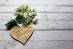 I wish you a happy birthday. The picture shows flowers and a wooden heart with the german text for the birthday royalty free stock images