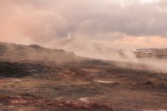 Geothermal steam rises in a field in Iceland. This picture shows a lighthouse in the distance and geothermal steam rising in the field in the foreground royalty free stock image