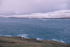 A lone red lighthouse in the faroe islands. This picture shows a lone red lighthouse in the faroe islands Stock Photo