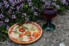 Pizza on a thyme field and red wine royalty free stock images