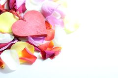 A red heart on rose petals royalty free stock photo