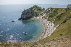 Blue waters and a boat - Durdle Door, Dorset, England. The picture shows some blue waters and a beach in Dorset, Durdle Door. It was taken on a sunny day in Royalty Free Stock Photos