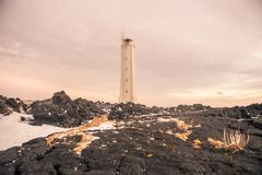 A tall lighthouse in Iceland. This picture shows a tall white lighthouse standing on a rocky hill in Iceland royalty free stock photography
