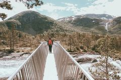 Man walks on a small bridge above a river in norway stock images
