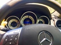 Mercedes benz c class fast driving. This picture shows us a steering wheel and dash board of a Mercedes Benz.steering wheel is looks like half circle.there is stock photos