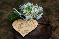 Happy birthday greetings. The picture shows a wooden heart with the german text for birthday and flowers on a tree trunk royalty free stock photography