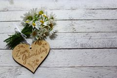 Happy birthday greetings. The picture shows a wooden heart with the german text for birthday and flowers on white wooden boards stock images