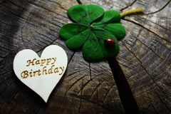 Happy birthday greetings. The picture shows a wooden heart with happy birthday greetings and lucky clover with a ladybird stock image