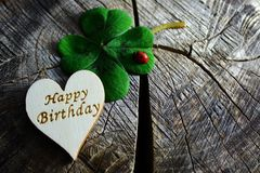 Happy birthday greetings. The picture shows a wooden heart with happy birthday greetings and lucky clover with a ladybird royalty free stock photo