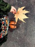Young girl, city, autumn and maple leaf. Musical notes on the street tiles. Royalty Free Stock Photography
