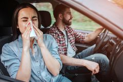 A picture of sick girl riding in car with young man. She is sneezing in napkin while he is paying attention to the road. Girl is suffering stock photos