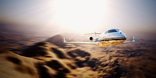 Picture of silver modern and luxury generic design private jet flying blue sky at sunrise.Uninhabited desert mountains Stock Photo