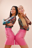 Picture of 2 sisters gorgeous happy smiling blonde and brunette sexy young women having fun together in leather pink dresses Royalty Free Stock Image