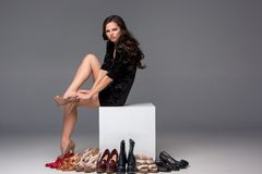 Picture of sitting woman trying on high heeled Stock Image