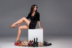 Picture of sitting woman trying on high heeled Stock Photos