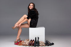 Picture of sitting woman trying on high heeled Royalty Free Stock Photo