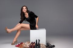 Picture of sitting woman trying on high heeled Stock Photography