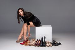 Picture of sitting woman trying on high heeled Stock Photo