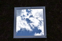 Picture of the sky. View of clouds in the sky looking in a mirror set on the ground Stock Photo