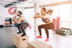 A picture of slim and well-built young man and woman doing jumps on platform. It is a hard exercise but they are doing. A picture of slim and well-built young Royalty Free Stock Photos