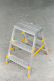 Picture of small foldable ladder on sidewalk. Picture of a small foldable ladder on sidewalk Royalty Free Stock Image