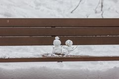 A picture of two snowman on a wooden bench. royalty free stock photo