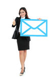 Picture of smiling businesswoman holding sign of envelope Stock Photos