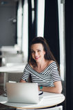 Picture of smiling woman using laptop in a cafe and looking at the camera. Royalty Free Stock Photos