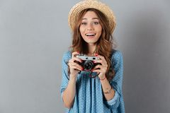 Smiling young caucasian woman photographer holding camera. Picture of smiling young caucasian woman photographer holding camera. Looking aside Stock Images