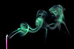 The picture of a smoking incense, isolated on black background. Green smoke. Stock Images