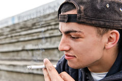 Picture about smoking. young man is laughing and smoking a cigar Stock Photo