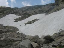 Snow high up in the mountains. A picture of snow high up in the mountains in Switserland taken on a cartrip during a vacation in the summer Stock Image