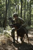 Picture of soldier in helmet with submachine gun and dog. On task in forest stock image